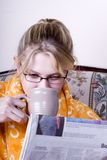 Girl with coffee and paper. Girl with towel around neck in morning drinking coffee and reading newspaper in home royalty free stock image