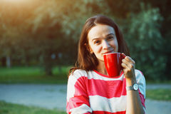 Girl with coffee in park Royalty Free Stock Photography