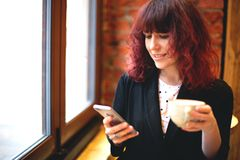 Girl with coffee and phone royalty free stock photos
