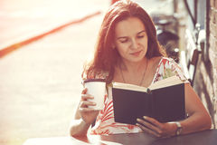 Girl with coffee reading book royalty free stock image