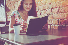 Girl with coffee reading book Royalty Free Stock Photos