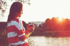 Girl with coffee at river sunrise. Pretty girl with morning coffee at river sunrise stock photography