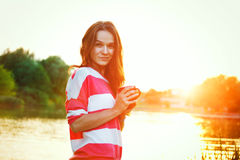 Girl with coffee at river sunrise Royalty Free Stock Photography