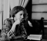 Girl at coffee shop. Sensual girl reading a book and drinking a coffee in a coffee shop Royalty Free Stock Images