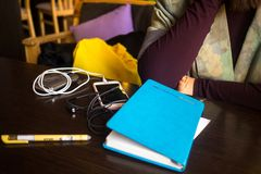 The girl in the coffee shop, writes in a notebook and listening music on the mobile phone stock image
