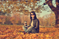 Girl with coffee sitting in park Stock Images