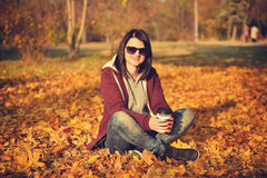 Girl with coffee sitting on yellow leaves Stock Photo