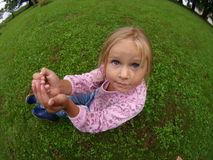 Girl with Coints. Girl sitting on the grass with coints in her hands stock images