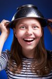 Girl with a colander on her head Royalty Free Stock Photo