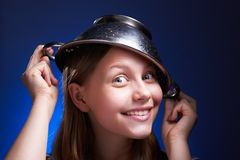 Girl with a colander on her head Stock Images