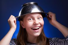 Girl with a colander on her head Royalty Free Stock Image