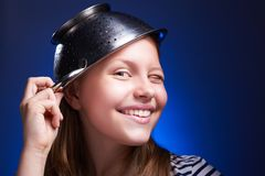 Girl with a colander on her head winking and smiling Stock Image
