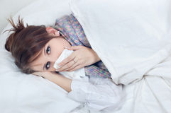 Girl with a cold. In bed Stock Images