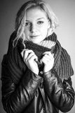 Girl with a cold. Girl holding a long home knitted scarf around her neck. Monochrome stock image