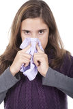 Girl with a cold blowing nose Royalty Free Stock Photo