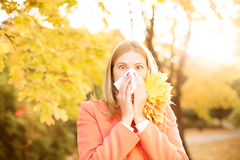 Girl with cold rhinitis on autumn background. Fall flu season. I. Ll sick sneezing woman. Handkerchief, vaccine against influenza virus Caught Cold Headache Stock Images