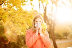 Girl with cold rhinitis on autumn background. Fall flu season. I Stock Photo