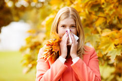 Girl with cold rhinitis on autumn background. Fall flu season. I. Ll sick sneezing woman. Handkerchief, vaccine against influenza virus Caught Cold Headache Royalty Free Stock Images