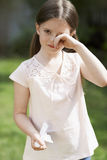 Girl With Cold Rubbing Eyes. Portrait of young girl with cold rubbing eyes in backyard Stock Photos