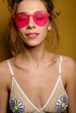 The girl with collected hair and the top of the swimsuit in the pink glasses is on a yellow background with closed eyes. Vertical photo Stock Images