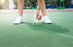 Girl collecting badminton ball on field. Girl collecting badminton ball on the field royalty free stock photos