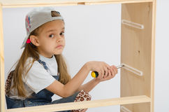 Girl collector of furniture with a screwdriver collects wooden cabinet Royalty Free Stock Photo