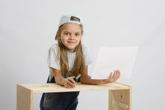 Girl collector of furniture with a screwdriver and drawing collects furniture Royalty Free Stock Image