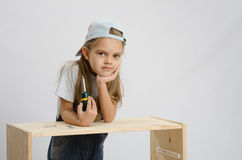 Girl collector of furniture with a screwdriver wearily leaned on the cabinet Stock Image