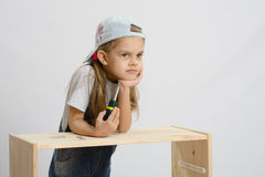 Girl collector of furniture with a screwdriver wearily leaned on the cabinet Royalty Free Stock Images