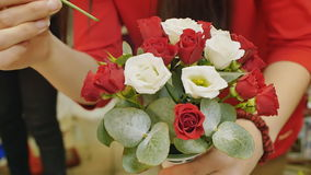 Girl collects a bouquet of roses. Preparations for the wedding, gift for a woman. hands closeup stock footage