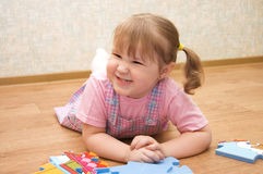 Girl collects puzzles in a room Royalty Free Stock Photo