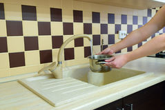 A girl collects water in a saucepan in a modern kitchen Royalty Free Stock Photography