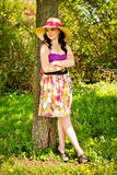 Girl in color dress and straw hat Stock Photos