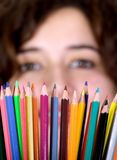 Girl with color pencils in front of her Stock Images