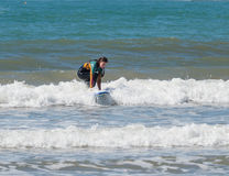 Girl in color waterproof suit exercising in surfing on board Stock Photo