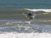 Girl in a color waterproof suit exercising in surfing on the board Royalty Free Stock Photography