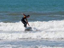 Girl in a color waterproof suit exercising in surfing on the board Stock Photos
