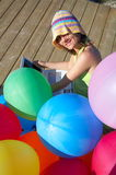 Girl with colored balloons using a lapt. Happy girl with a bunch of colored balloons using a laptop Royalty Free Stock Photography