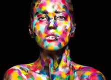 Girl with colored face painted. Art beauty image Stock Photography