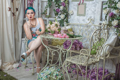 Girl with colored hair in the room. Bright girl with colored hair sitting in a room with flowers Royalty Free Stock Photography