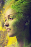 Girl with colored powder. Exploding around her Stock Photos