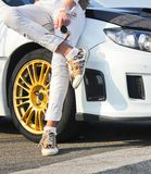 Girl in colored sneakers shoes and in white trousers on background of white car. Girl on car background royalty free stock images