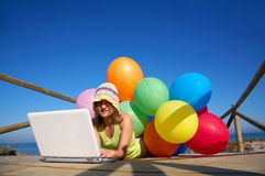 Girl with colorful alloons using a laptop. Girl with a bunch of colored balloons using a laptop on the beach stock photo