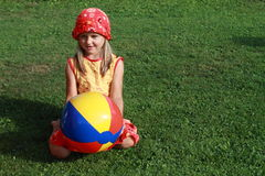 Girl with colorful ball. Little girl in red and yellow dress kneeing with colorful ball royalty free stock images