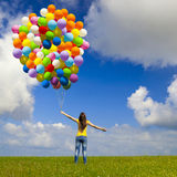 Girl with colorful balloons. Happy young woman with colorful balloons on a green meadow royalty free stock images