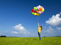 Girl with colorful balloons. Happy young woman with colorful balloons on a green meadow stock photo