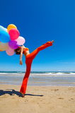 Girl with colorful balloons on the beach Stock Photography