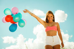 Girl with colorful balloons on beach Stock Image