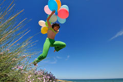 Girl with colorful balloons jumping Stock Image