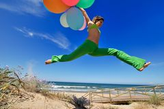 Girl with colorful balloons jumping Royalty Free Stock Image